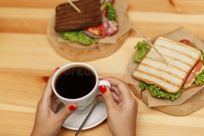 Twee sandwiches en kop van hete koffie, op houten lijst De vrouwenhanden neemt kop royalty-vrije stock afbeelding