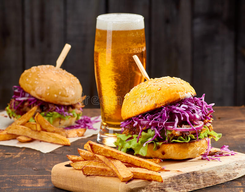 Twee sandwiches met getrokken varkensvlees, frieten en glas bier op houten achtergrond stock foto's