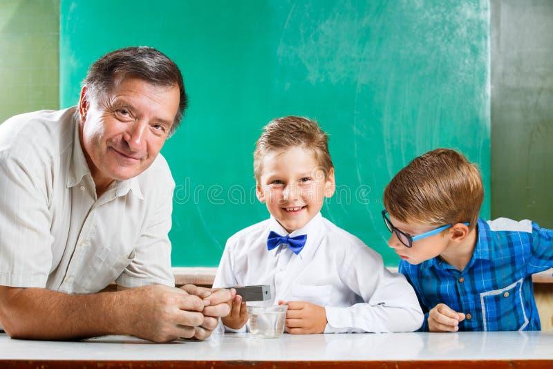 Twee schooljongens en hun leraar in klasse stock foto's