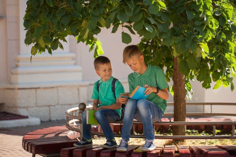 Twee schoolkinderen zitten onder een boom en lezen boeken op een zonnige de zomerdag royalty-vrije stock fotografie