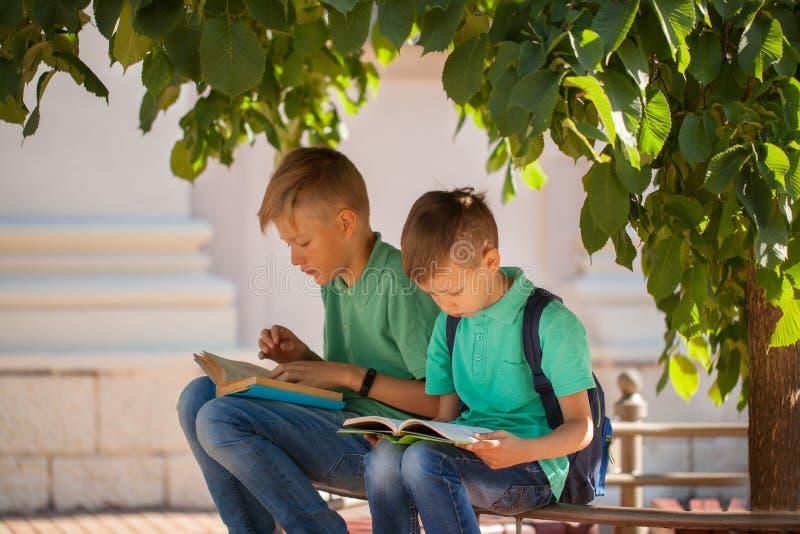 Twee schoolkinderen zitten onder een boom en lezen boeken op een zonnige de zomerdag stock foto's