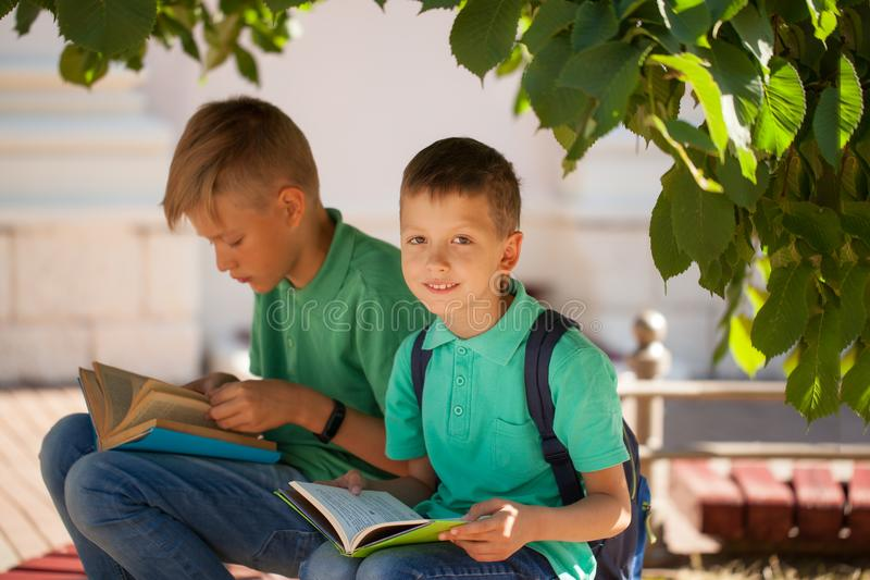 Twee schoolkinderen zitten onder een boom en lezen boeken op een zonnige de zomerdag royalty-vrije stock afbeelding