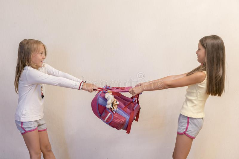 Twee schoolmeisjes die voor schoolrugzak vechten Conflict in school tussen studenten Conflict in school tussen schoolmeisjes stock afbeelding