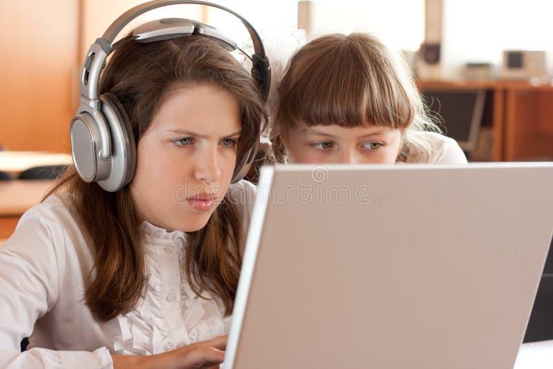 Twee schoolmeisjes met notitieboekje stock foto