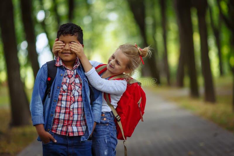 Twee schoolvrienden die pret in park hebben Kaukasisch Meisje die ogen behandelen aan verraste afro Amerikaanse jongen stock foto's
