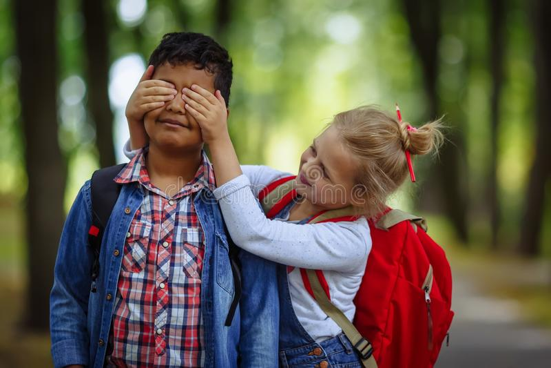 Twee schoolvrienden die pret in park hebben Kaukasisch Meisje die ogen behandelen aan verraste afro Amerikaanse jongen stock fotografie