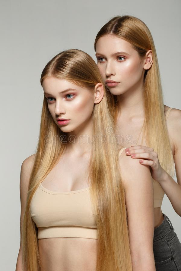 Twee sexy aantrekkelijke tweelingenvrouw met blonde het lange haar stellen in glamourmake-up stock foto's