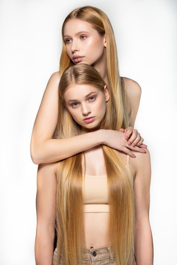 Twee sexy aantrekkelijke tweelingenvrouw met blonde het lange haar stellen in glamourmake-up, vervanger achter elkaar, die in ste stock afbeeldingen