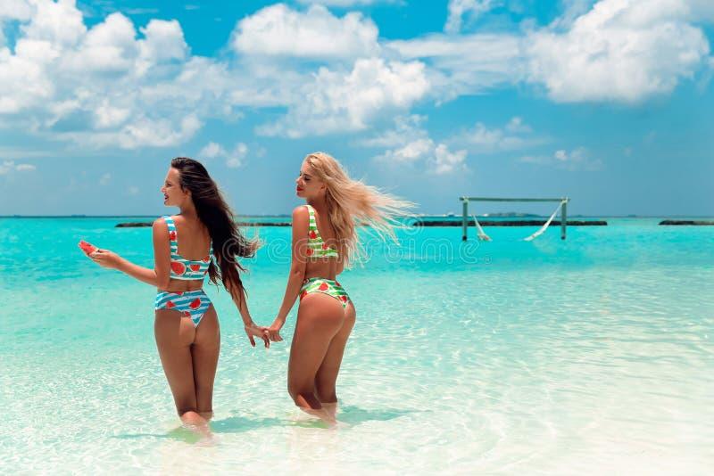 Twee sexy bikinimodellen die pret op tropisch strand, het exotische eiland van de Maldiven hebben De vakantie van de zomer Gelukk stock afbeelding