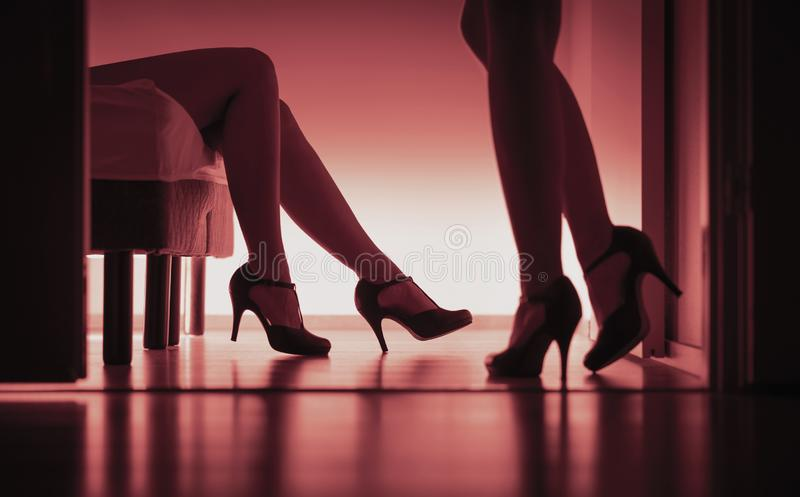 Twee sexy dames in hoge hielen Vrouwen die geslacht hebben Lesbiennes, prostituees of escortes Lang benensilhouet in rood licht royalty-vrije stock fotografie