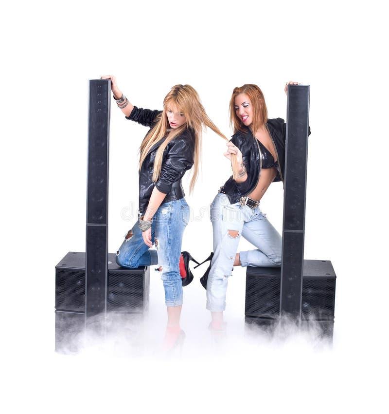 Twee sexy meisjes die met audiomateriaal stellen stock afbeeldingen