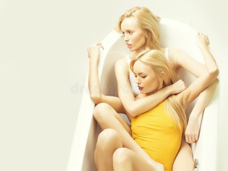 Twee sexy vrouwen die in wit bad liggen royalty-vrije stock fotografie