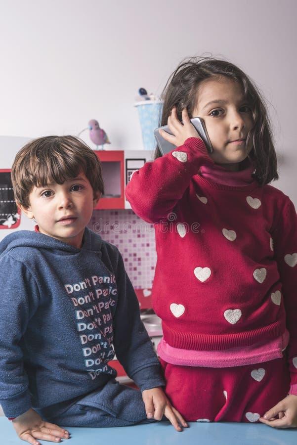 Twee siblings die in stuk speelgoed keuken spelen stock foto's