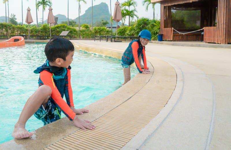 Twee siblings in het spelen samen in het parkpool van Wateraqua stock afbeelding