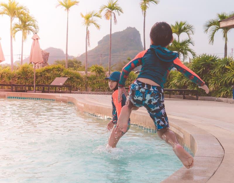 Twee siblings in het springen neer in het parkpool van Wateraqua stock foto's