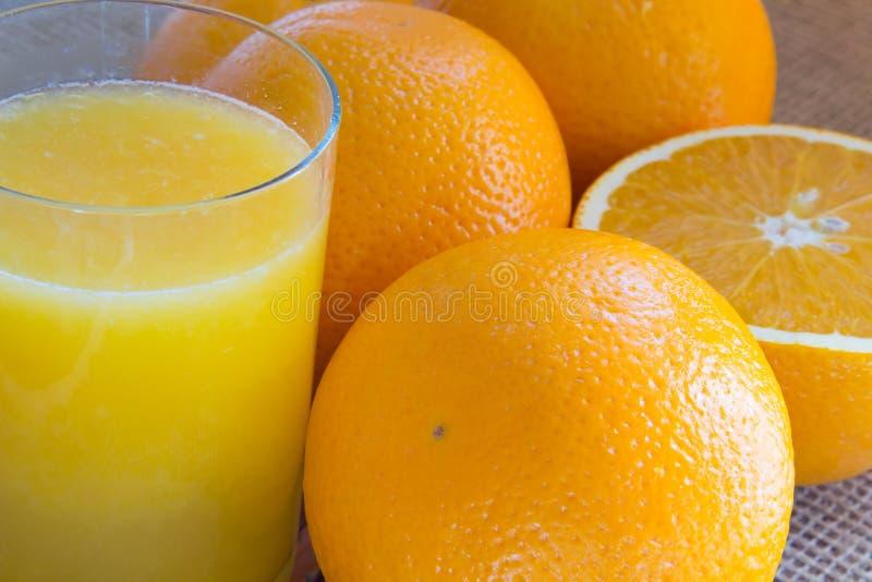 Twee sinaasappelen en de helft van een sinaasappel; een glas sap royalty-vrije stock afbeeldingen