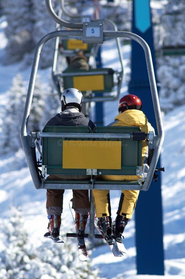 Twee skiërs op lift stock foto