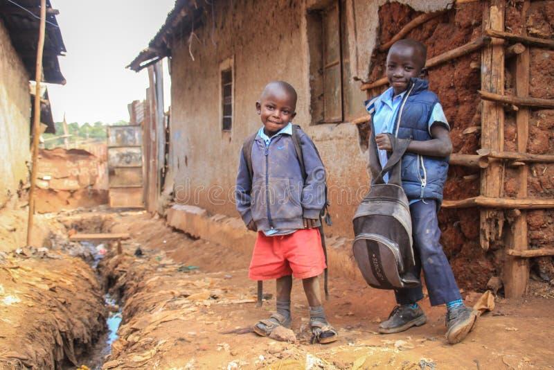 Twee slechte zwarte jongens in krottenwijken gaan naar school in een slecht district van Kibera stock afbeelding