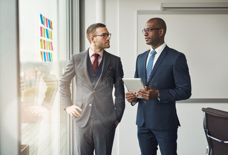 Twee slimme bedrijfsleiders in een bespreking stock fotografie