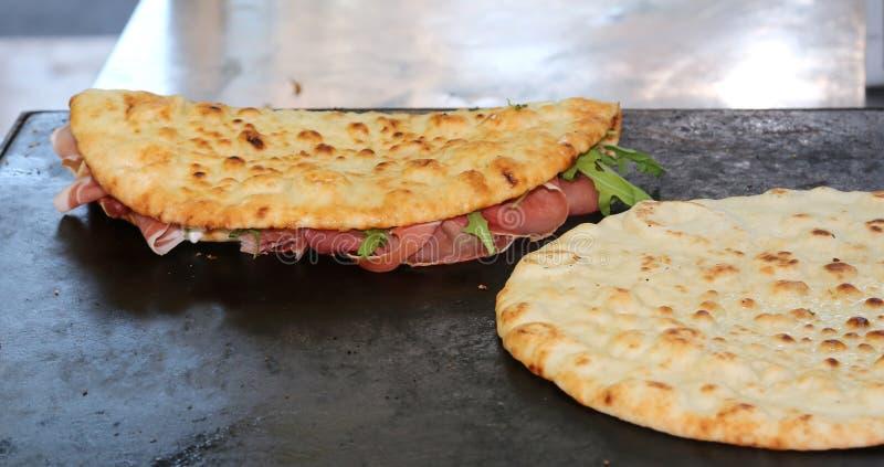Twee smakelijke piadines die met ham en kaas op de warmhoudplaat wordt gevuld stock foto