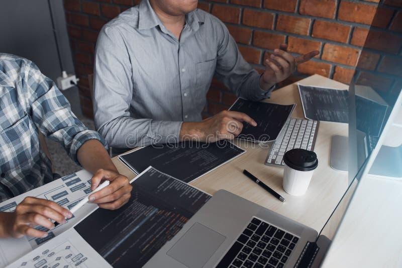 Twee softwareontwikkelaars gebruiken computers om samen met hun partner bij het bureau te werken stock foto's