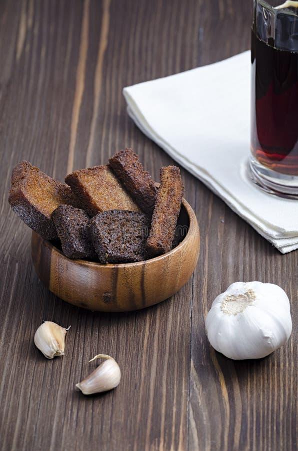 Twee soorten gebraden brood in een houten plaat met knoflook en drank in een glas op een houten achtergrond royalty-vrije stock foto