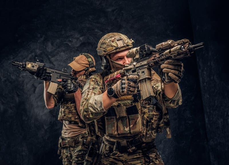 Twee speciale krachtenmilitairen in volledige beschermingsmiddelholding vallen geweren en het streven naar de doelstellingen aan  stock fotografie