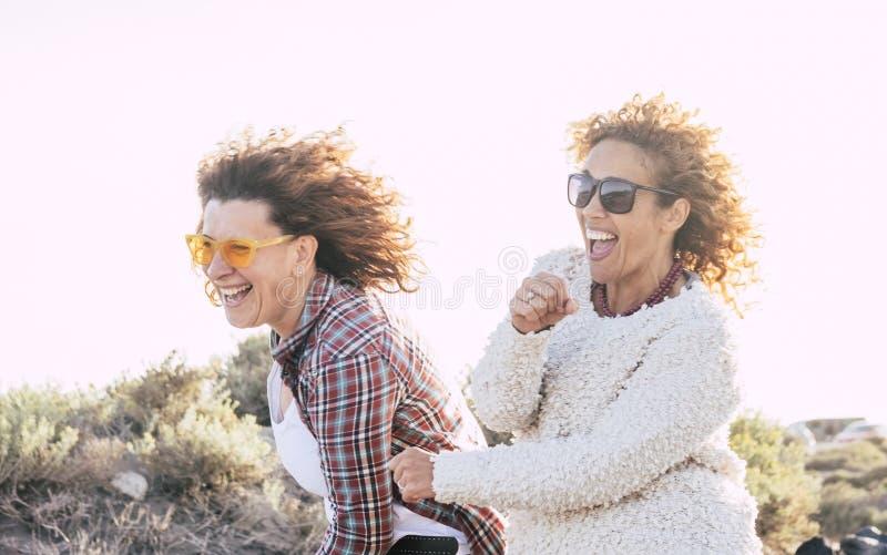 Twee speelse gelukkige vrolijke middenleeftijdsvrouwen hebben partij van pret die samen - gekheid en speels concept voor aardige  stock afbeelding