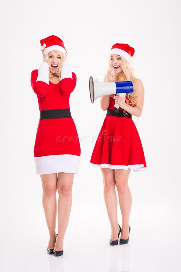 Twee speelse tweelingen die van blondezusters gebruikend megafoon gekscheren royalty-vrije stock foto