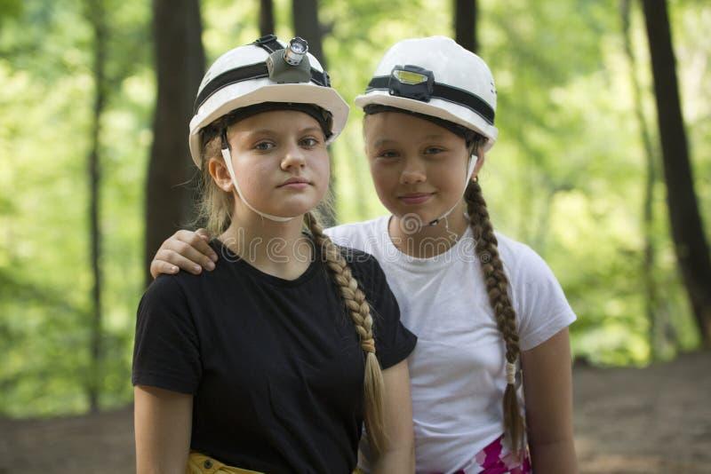 Twee speleologen van tienermeisjes in helmen in het bos bij zonnige D stock foto
