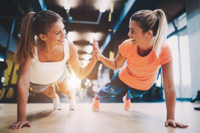 Twee sportieve meisjes die duw UPS in gymnastiek doen stock foto