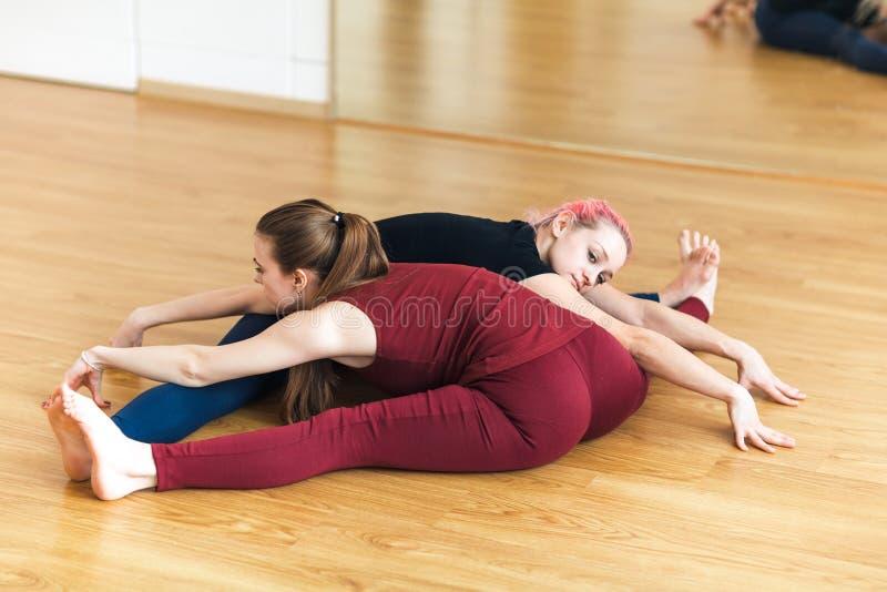 Twee sportieve meisjes die in gymnastiek acroyoga, yoga met partner doen, Brede hoek zetten Voorwaartse Kromming, Upavishtha Kona stock foto
