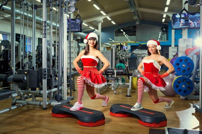 Twee sportieve meisjes in Santa Claus-kostuums bij de gymnastiek in Kerstmis stock foto