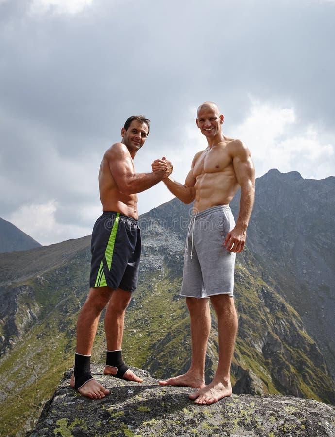 Twee sportieve mensen die handen schudden stock fotografie