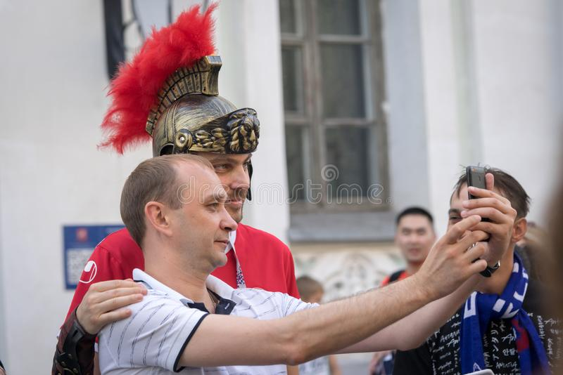 Twee sportventilators één van hen in antieke helm die selfie samen maken stock fotografie