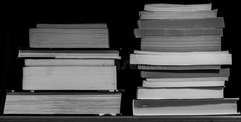 Twee stapels van boeken op een plank, in zwart-wit royalty-vrije stock afbeeldingen