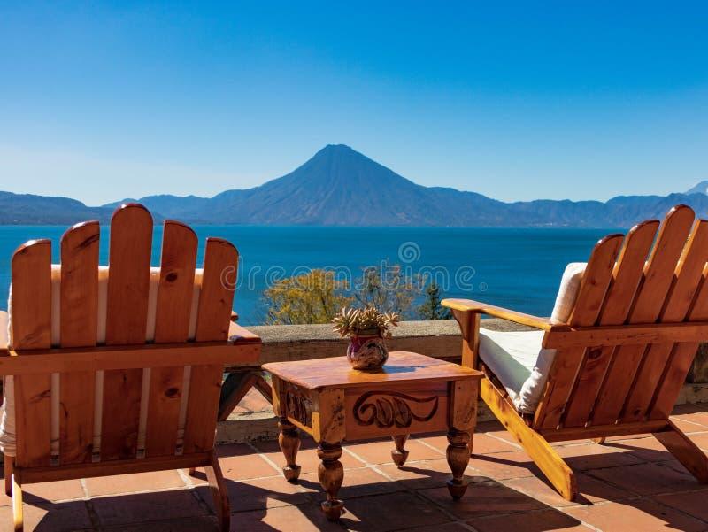 Twee stoelen met lijst die uit over meer en vulkaan kijken stock afbeelding
