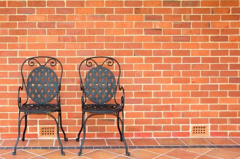 Twee stoelen tegen bakstenen muur stock foto