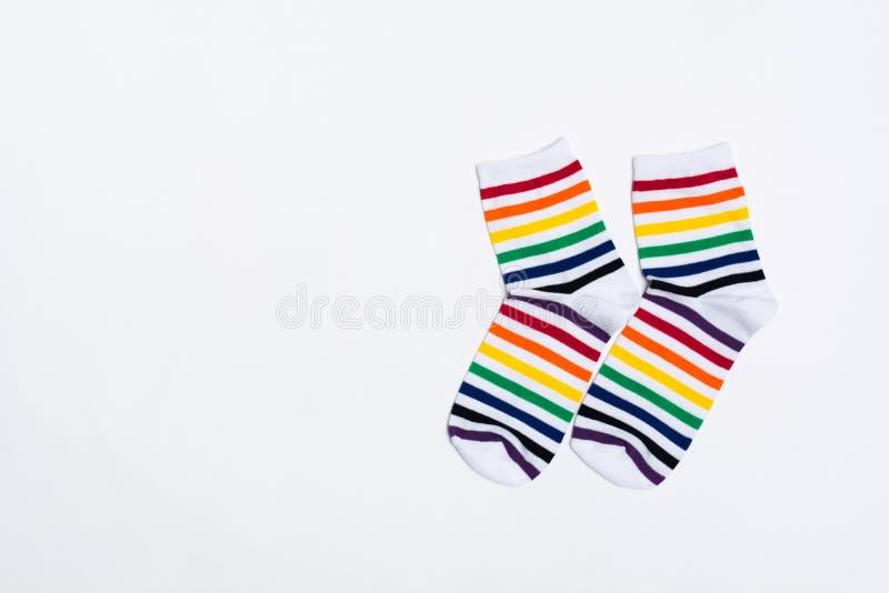 Twee stoffen witte sokken met kleurrijk gestreept patroon over witte achtergrond met exemplaarruimte Textiel warme kleren voor vo stock fotografie