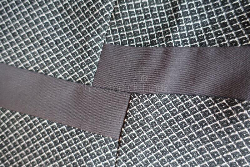 Twee stroken van bruine die stof aan grijze worden genaaid stock foto