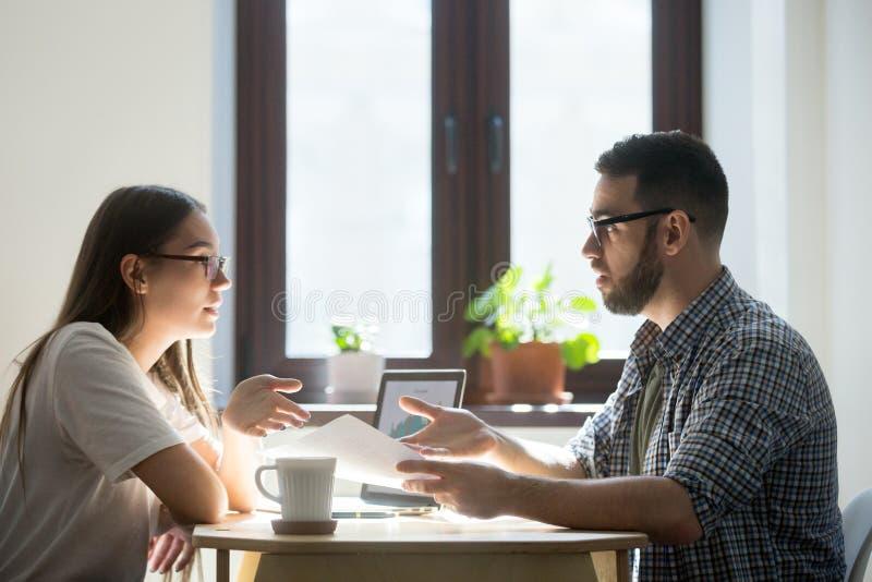 Twee studenten die koffie drinken en een nieuw project bespreken royalty-vrije stock afbeelding