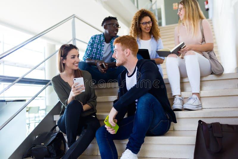 Twee studenten die zij mobiele telefoon op een universiteit gebruiken royalty-vrije stock afbeeldingen