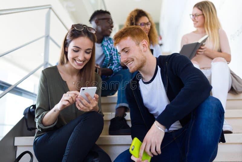 Twee studenten die zij mobiele telefoon op een universiteit gebruiken royalty-vrije stock afbeelding