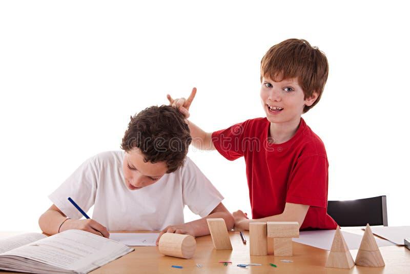 Twee studenten in het klaslokaal, dat lelijk gebaar maakt royalty-vrije stock foto