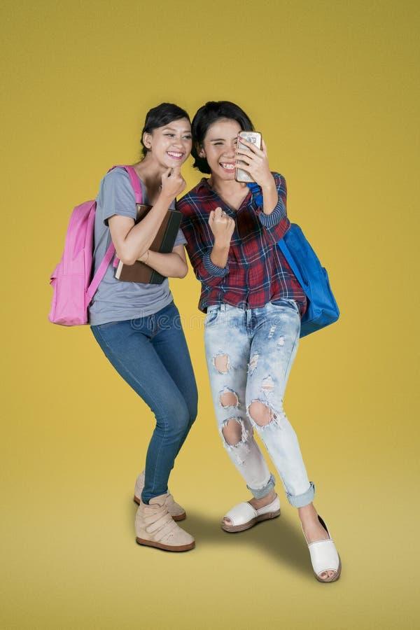 Twee studenten vieren hun succes stock foto