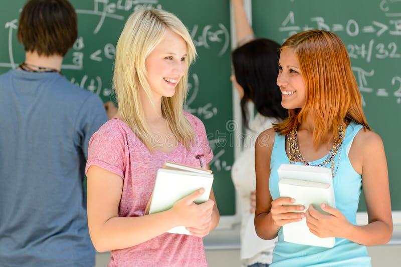 Twee studentvrienden die wiskundeles spreken stock afbeeldingen