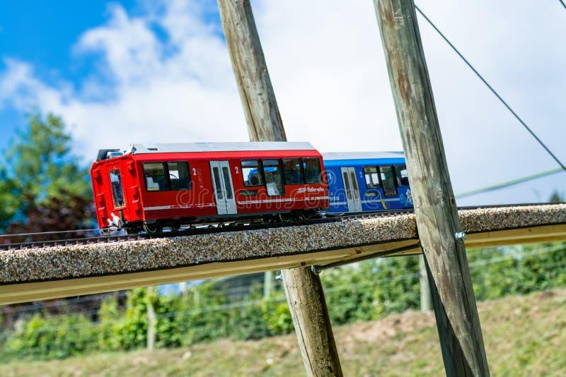 Twee stuk speelgoed locomotieven, één blauw en één rood, op een houten brug royalty-vrije stock foto's