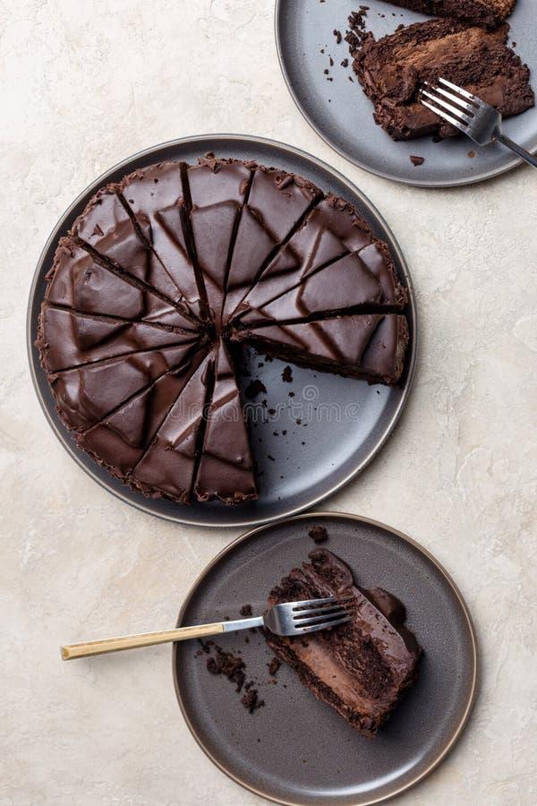 Twee stukken van chocoladecake met gehele cake op lichte achtergrond royalty-vrije stock foto's