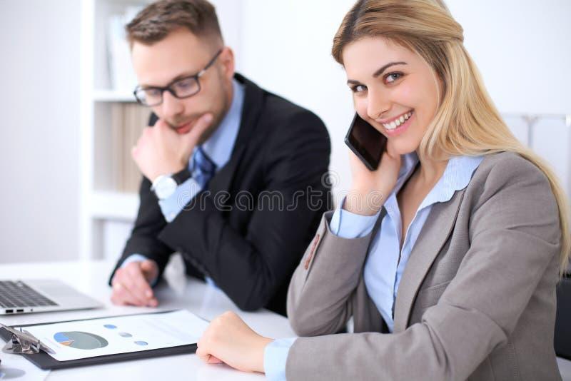 Twee succesvolle partners die op vergadering in bureau werken Nadruk op blonde terwijl het spreken telefonisch royalty-vrije stock foto