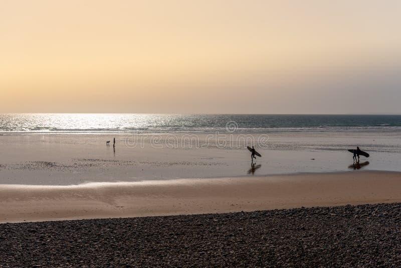 Twee surfers op een strand bij zonsondergang royalty-vrije stock fotografie